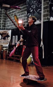 Alex Haycock juggling clubs and balancing on a rolabola